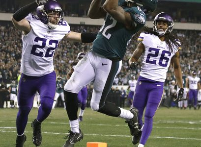 Philadelphia Eagles' Torrey Smith catches a touchdown pass in front of Minnesota Vikings' Trae Waynes (26) and Harrison Smith (22) during the second half of the NFL football NFC championship game Sunday, Jan. 21, 2018, in Philadelphia. (AP Photo/Matt Slocum)