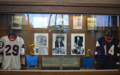 Septembers historical display case features two old Trojan team jerseys and an old helmet. It also displays pictures of Coach Distasio and two football championship trophies. Additionally, there are also the Coach Distasio Memorial Award along with old pictures of football players.